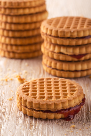 greased: Vertical photo of several stacks of golden biscuits. Biscuits are with red berry homemade marmalade. Biscuits are placed on light white wooden board. Several crumbs are spilled around. Stock Photo