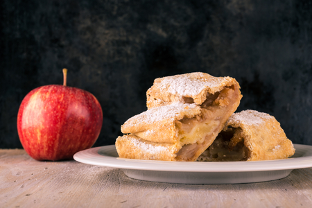 Horizontal photo with traditional apple strudel with fruit and powder sugar on white plate. Single apple fruit is next to pastry on wooden board with vintage worn black baking tray background.