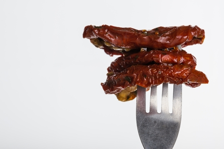 Horizontal photo of three dried tomatoes which are impaled on metal fork with wooden holder on white background. Slice of vegetable were marinated in olive virgin oil.