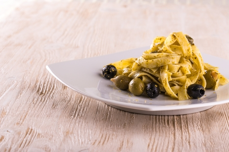 caper: Horizontal photo single portion of tagliatelle pasta with green pesto on white  plate and vintage wooden board. The capers, black and green olives with almonds are spilled around.