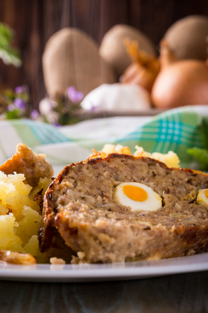 Vertical photo with two slices of homemade Easter meatloaf which is filled by quail eggs and is served with meshed onion potatoes on white plate. Ingredients like herbs and vegetable are around.