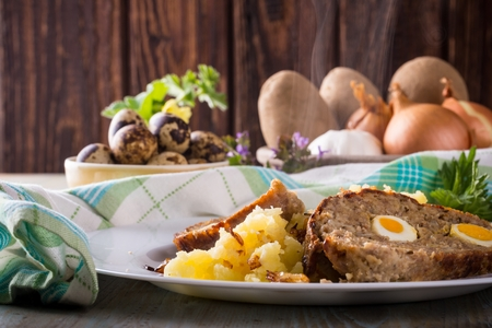 Horizontal photo with two slices of homemade Easter meatloaf which is filled by quail eggs and is served with meshed onion potatoes on white plate. Ingredients like herbs and vegetable are around.