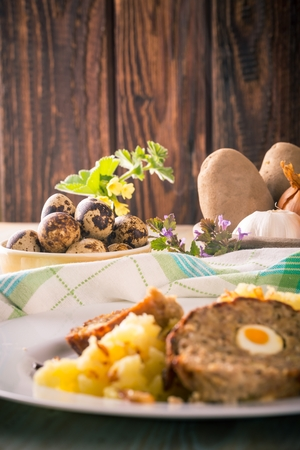 Vertical photo of yellow bowl full of quail eggs next to portion of Easter meatloaf filled by eggs with meshed potatoes and pan with vegetable. Few flowers and herbs are around the food. Stock Photo