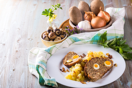 Horizontal photo with portion of homemade meatloaf from pork and beef minced meat and filled by quail eggs on white plate with meshed potatoes. Other ingredients are around with green cloth. Stock Photo