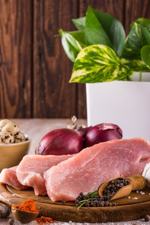 Vertical photo of three slices of raw pork meat which are placed on dark wooden board with whole pepper, milled red capsicum, few pieces of quail eggs, salt, red onions and green flower in background.