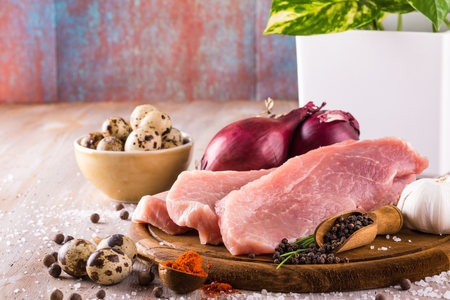 Horizontal photo with few slices of raw pork meat on wooden plate with spice as pepper or paprika around together with vegetable and quail eggs in bowl and next to meat. Few salt grains are present. Stock Photo