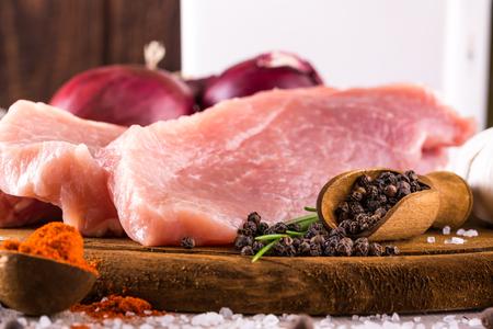 Horizontální fotografie vinobraní dřevěné lžíce plné pepřových semen. Spice je příliš rozlité kolem sušené papriky nebo soli. Banda pažitky je vedle surového vepřového masa nakrájeného na několik plátků.