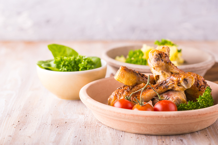 meshed: Horizontal photo with three bowls. First contains baked chicken legs with crunchy skin, parsley and tomatoes. Second meshed herb potatoes and one with green spinach salad.