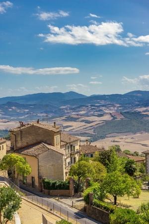イタリア トスカーナの歴史的な町の側で造られる古い素朴な家と縦の写真を。丘、岩、オリーブの木と森の風景は、バック グラウンドでです。曇り