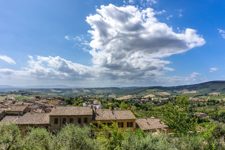 Horizontal photo with few rustic houses which are built on side of historic town in Tuscany Italy. The landscape with hills, rocks, olive trees and forests is in background. Sky is cloudy. Stock Photo