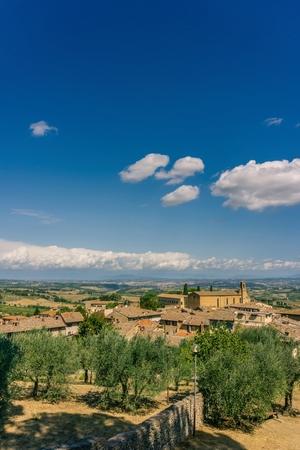イタリアのトスカーナの風景の中に縦の写真を。1 つの教会といくつかの歴史的な建物は、フォア グラウンド、いくつかのオリーブの木丘や背景の 写真素材