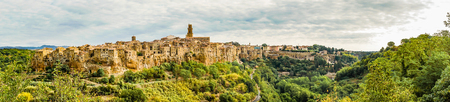 blue widescreen widescreen: Horizontal panoramic photo of historic ancient town Pitigliano which is located in Italy Tuscany. Town is build on tuf ash rock. The roads, hills with forests and gardens are visible around.