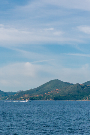 Vertical photo of a boat which sail in Mediterranean Sea. The boat is in front of coast with few rocks of mountains in Tuscany Italy. The rocks are near the Livorno harbor.