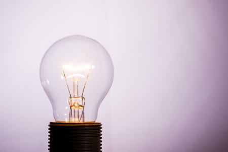 Horizontal photo with single glass bulb. The bulb is switched on and the wire inside is hot and is shining. The background is light with shadows in corners. The bulb is in socket.