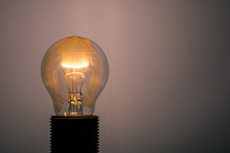 Horizontal photo of single glass bulb placed in the socket on dark background. The fire and flame inside is caused by burning wire. The orange smoke is filling the inner space. Stock Photo