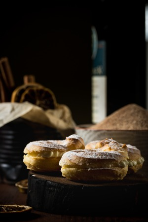 Vertical photo of three homemade cream puffs. Sweet cake is filled by whipped cream and placed on dark wooden board with bottle of red wine, cinnamon sticks in can and sugar.