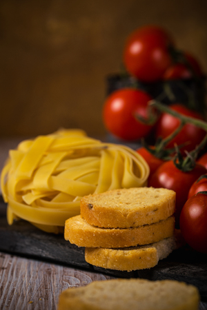 Vertical photo with few pieces of bruschetta rings with herbs and garlic which are stacked on vintage wooden board. The portion of tagliatelle is next to red cherry tomatoes on branch.