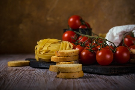 Horizontal photo with few pieces of bruschetta rings with herbs and garlic which are stacked on vintage wooden board. The portion of tagliatelle is next to red cherry tomatoes on branch.