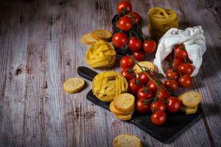 Horizontal photo of several twigs with red cherry tomatoes. Vegetable is placed on wooden vintage board, old worn can or in white paper bag. Tagliatelle and bruschetta rings are around. Stock Photo