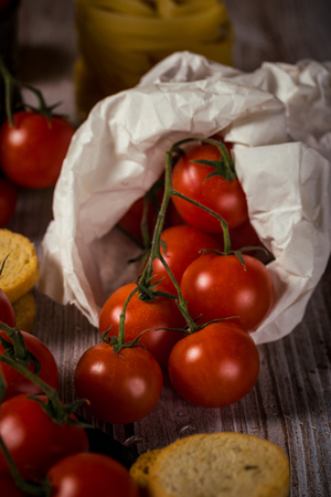 Vertical photo with few twigs with small red cherry tomatoes. Vegetable is in white paper bag which is placed on wooden vintage board with worn surface with bruschetta pieces around.