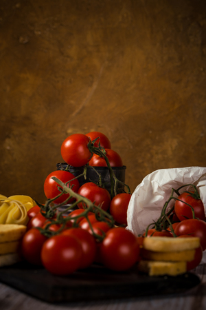 Vertical photo with small red cherry tomatoes which are on green twig and placed in vintage metal worn can. Tagliatelle and bruscheta rings are placed next to vegetable on wooden board.