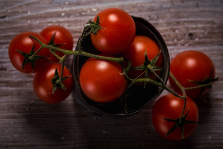 Horizontal photo with top view on several twigs of small red cherry tomatoes. Vegetable is placed in old worn metal can and pendent on vintage wooden board with damaged surface color.
