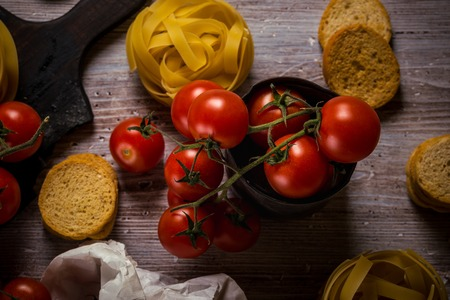 Horizontal photo with small red cherry tomatoes which are on green twig and placed in vintage metal worn can. Tagliatelle and bruschetta rings are placed next to vegetable on wooden board.