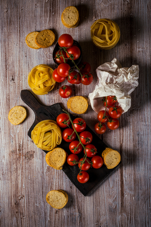 Vertical photo of several twigs with red cherry tomatoes. Vegetable is placed on wooden vintage board, old worn can or in white paper bag. Tagliatelle and bruschetta rings are around.