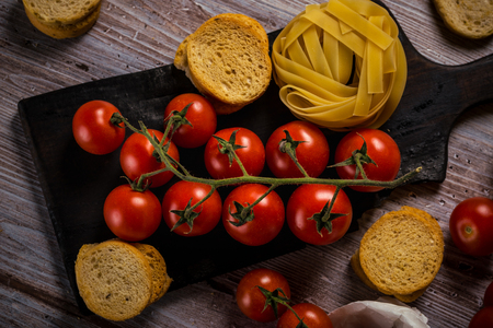 Horizontal photo with top view on twig with red cherry tomatoes which are placed on old chopping board and wooden table with vintage color. Bruschetta rings and tagliatelle are around. Stock Photo