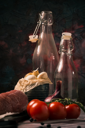 Vertical photo with old worn can which is full of white garlic cloves. The can is next to red cherry tomatoes, whole tenderloin pork meat and vintage glass bottles.