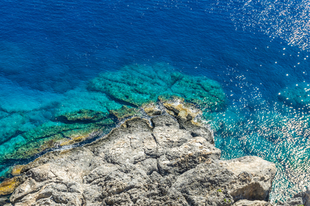 Horizontal photo with view down on rocky reef with blue sea around. Reef is under acropolis in Rhodos town Lindos captured in sunny summer day.