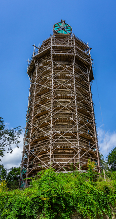 Vertical photo of ancient tower. The tower has wooden scaffolding and crane build according historical rules. Green trees and bush is in front. The sky is blue with few clouds.