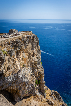 Vertical photo of a part of ancient acropolis above Mediterranean Sea and Lindos town. Acropolis is on Rhodes island. Blue sea and clear sky is visible in background behind rock. Stock Photo