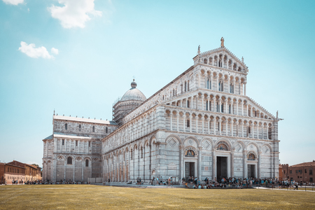 Horizontal photo with famous Piazza del Duomo cathedral. Building is placed on Piazza dei Miracoli with leaning tower. Grass is already brown and sky is light blue with few clouds. 免版税图像