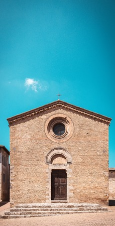 Vertical photo of small italian church. Building is in famous italian town San Gimignano in Tuscany.