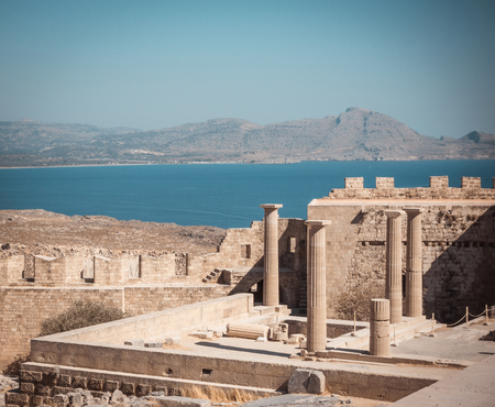 Horizontal photo with several pillars of Lindos Acropolis. Acropolys is on Rhodes island in Mediterranean Sea. Sea and sky is blue. Few rocks and hills are visible in background. 免版税图像
