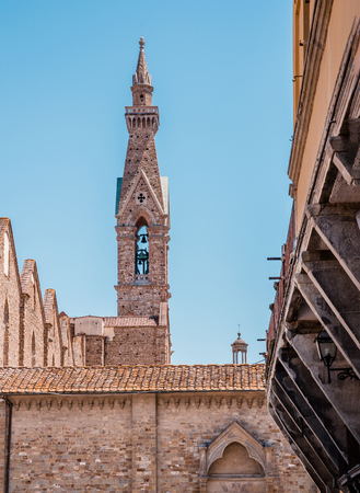 Vertical photo with narrow and high tower with bell in famous Italy city Florence. City is in Tuscany. Sky is blue without clouds. Few ancients buildings from bricks are in foreground. Archivio Fotografico - 114561765