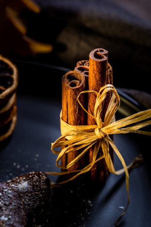 Vertical photo with several brown cinnamon sticks bonded by natural cord. Sticks are on black plate with chocolate sweets and stacked dry orange rings. Plate is on wooden board.