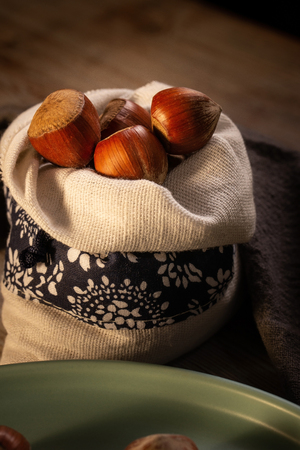 Vertical photo of several hazelnuts. Nuts are whole with shells with brown color. Nuts are placed in linen bag with white color and blue stripe. Bag is placed on wooden board with vintage color. Stock Photo