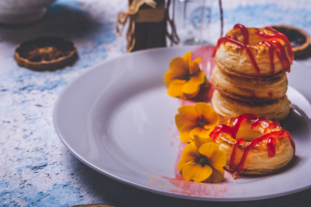 Horizontal photo with several donuts made from puff pastry dough. Red strawberry topping is spilled on rings. Donuts are placed on white plate with few yellow blooms.