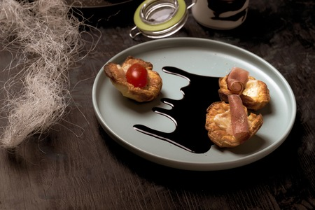 Horizontal photo of blue plate with puff pastry cups. Cups are stuffed by melted cheese. Ham and red tomatoes are on baked pastries. Dark sauce is spilled on plate. Plate is on wooden board.