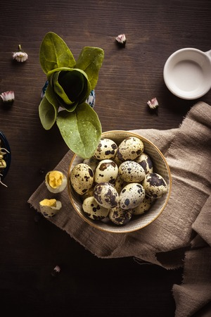 Vertical photo with top view on ceramic bowl full of quail eggs. Eggs have nice texture with brown spots. Bowl is placed on light cloth and dark wooden board.