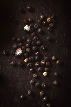 Vertical photo with top view on dark wooden board which is full of spilled juniper berries. Berries have dark blue color. Few daisy blooms with white and red color and on the board. Stock Photo