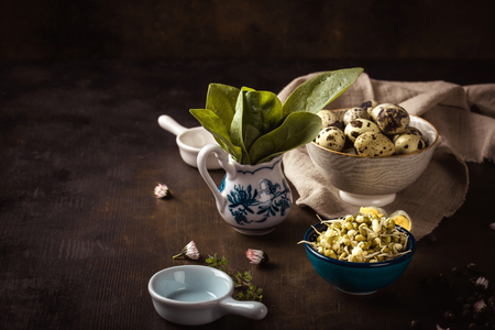 Horizontal photo of vintage wooden board with several bowls which contain mung bean sprouts, quail eggs and spinach. Light cloth is under one bowl. Zdjęcie Seryjne