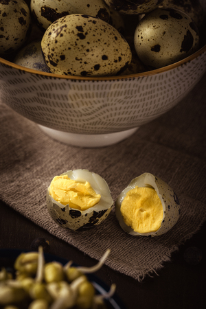 Vertical photo of single boiled quail egg broken in the middle. Other quail eggs are in bowl in background. eggs are placed on wooden board with mung bean sprouts. Stock Photo