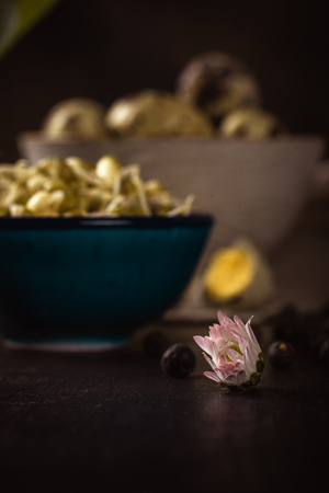 Vertical photo of single daisy bloom with white and red color. Bloom is placed on dark wooden board with mung bean sprouts and quail eggs.