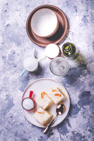 Vertical photo of few pieces of homemade cakes. Cake are from light dough with cream topping which is full of tangerine pieces. Cup with creamed milk is on the plate with spoon.