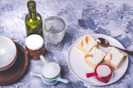 Horizontal photo of few pieces of homemade cakes. Cake are from light dough with cream topping which is full of tangerine pieces. Cup with creamed milk is on the plate with spoon.
