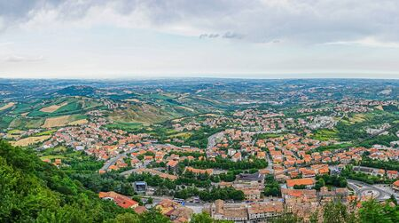 Horizontal photo with view downhill from San Marino town on other villages. The sea shore is visible in the background. Sky is with dramatic clouds. Several trees are among buildings. Stock Photo - 129595680