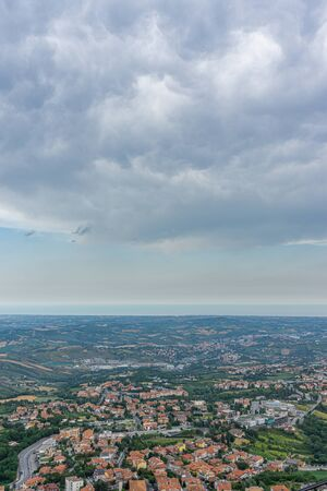 Vertical photo with view downhill from San Marino town on other villages. The sea shore is visible in the background. Sky is with dramatic clouds. Several trees are among buildings. Stock Photo - 129595682